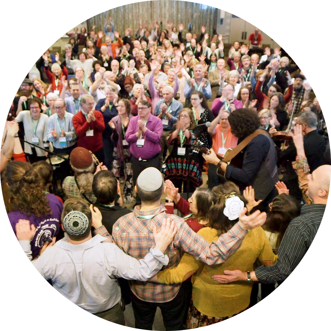 Image from people standing during a concert at a pervious Reconstructing Judaism convention.  Everyone is standing, clapping, raising hands in the air with a joyful look on their faces.